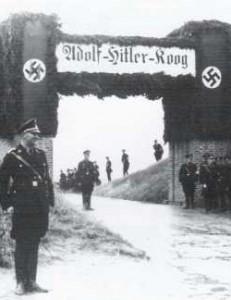 Männer der SS warten am 29.8.1935 an einer festlich geschmückten Stöpe auf die Ankunft Adolf Hitlers