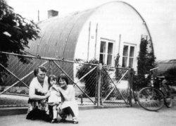 Nissenhütte in Bredstedt 1955. Die in Kanada erfundenen Baracken aus gebogenem Wellblech kamen mit den Alliierten nach dem Zweiten Weltkrieg nach Deutschland. Obwohl in Schleswig-Holstein nicht viele Nissenhütten aufgebaut wurden, sind sie zu einem Symbol der Notzeit nach dem Krieg geworden.