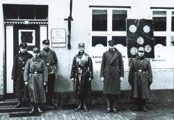 """Boykott des Geschäftes von Elke Blumann in der Rendsburger Kronprinzenstraße 8 am 1. April 1933. Elke Blumann wurde 1941 nach Minsk deportiert und gilt als """"verschollen"""". Auffällig die noch bunt zusammengesuchen Uniformen und das Schild mit den fünf Punkten: es war dem Verkehrsschild """"Einfahrt verboten"""" nachempfunden"""