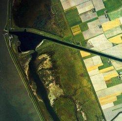 Der Hauke-Haien-Koog. Gut erkennbar das neue Ackerland und die Speicherbecken, die inzwischen auch als Rastreservate für Vögel eine wichtige Naturschutzfunktion erfüllen